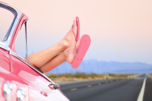 Freedom car travel concept - woman relaxing with feet out of win